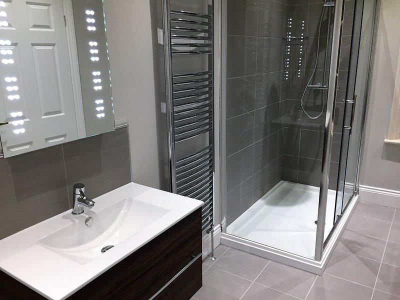 RdC salle de bain avec grande douche, lavabo, wc, miroir LED et point de rasage