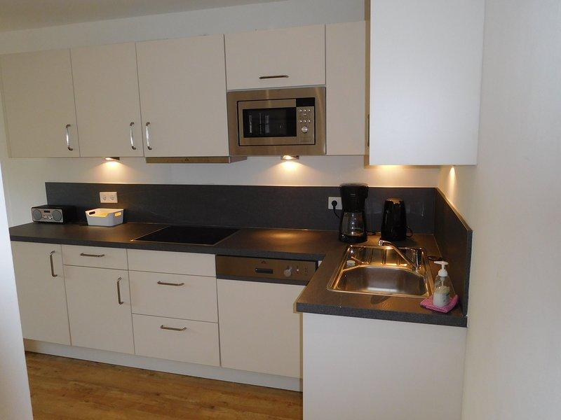 Cozinha com máquina de lavar louça, microondas, máquina de café (filtro), panela de água.
