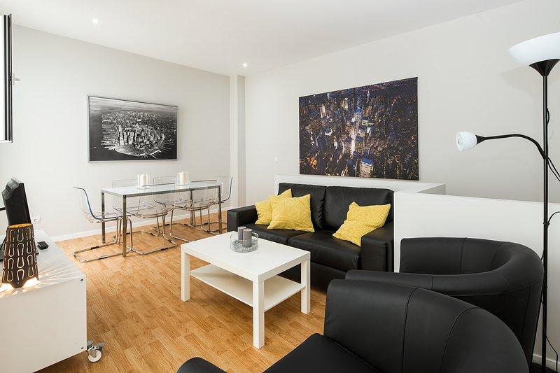 Wohnbereich mit Sofa, 2 Sessel, Couchtisch und TV.