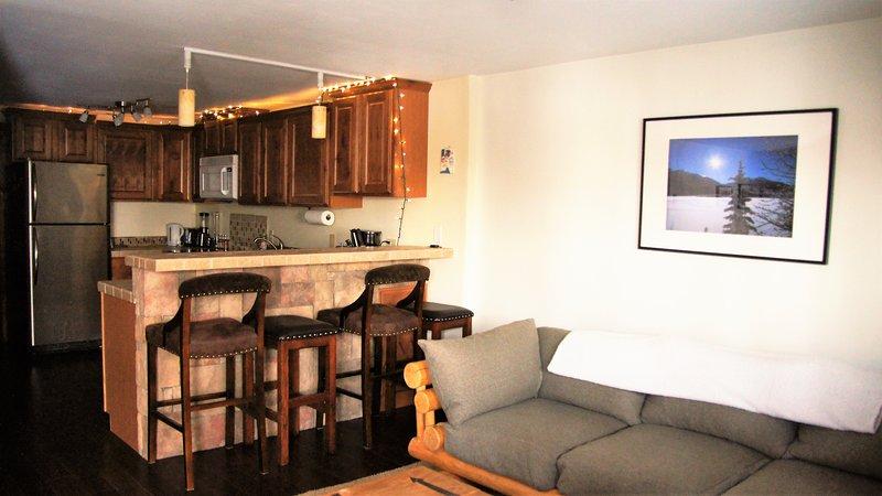 La sala de estar conduce a la cocina, que cuenta con barra de asientos para cuatro.