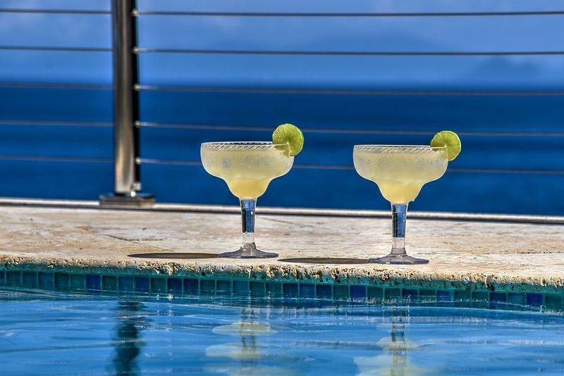 Njut av en Margarita, när man sitter i poolen, titta på panorama ner utsikt ö havet.