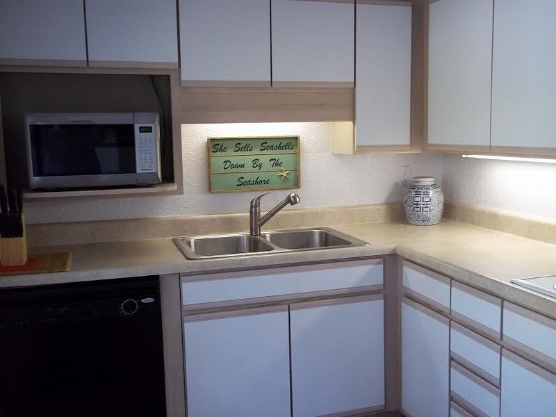 Kitchen with Cuisinart convection/microwave oven, dishwasher, fridge with ice-maker.