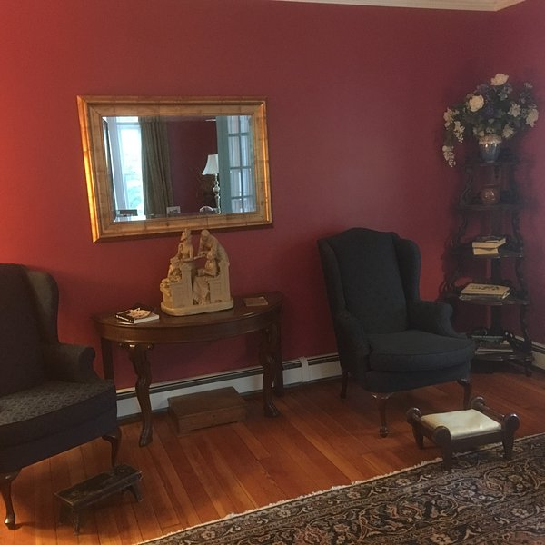LIVING ROOM. ANTIQUE STATUARY. WING CHAIRS.  WOOD FLOOR. PERSIAN RUG.