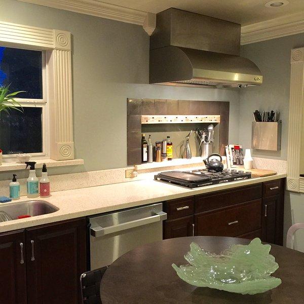 La cuisine a des ustensiles de cuisine et ustensiles de cuisine ainsi que des épices et des bases de cuisson.