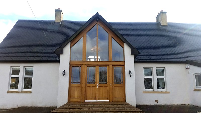 A uniquley designed main entrance with large doors and glass views to the hall way.