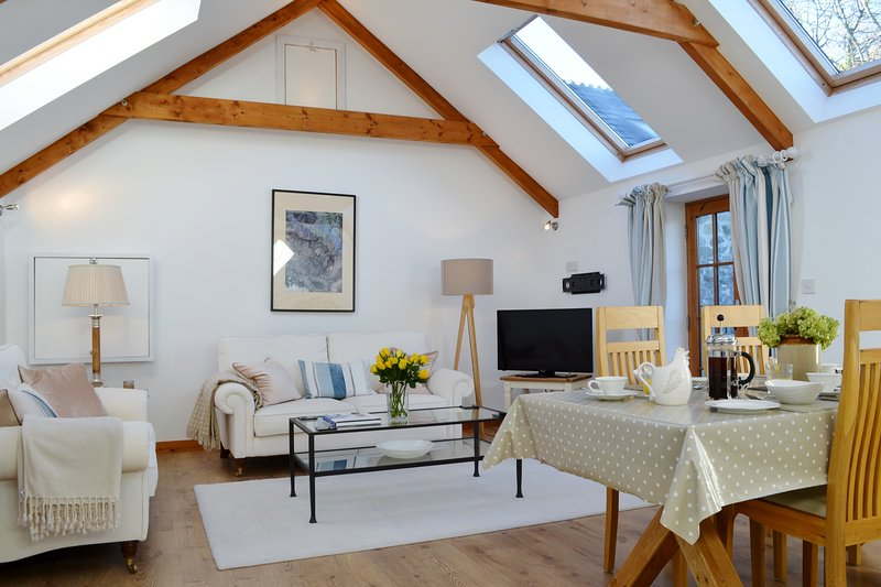 The airy open-plan sitting and dining area under the eaves