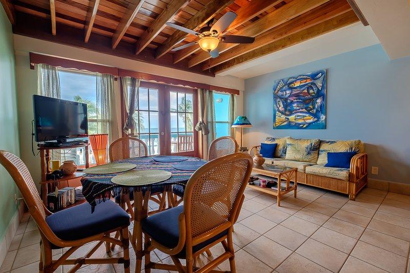 un coin salon et salle à manger magnifique avec de hauts plafonds avec poutres apparentes! couleurs chaudes tout au long! charme