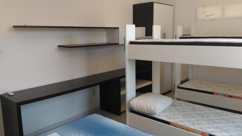 Slaapkamer met een tweepersoonsbed, twee stapelbedden, kasten en airconditioning.
