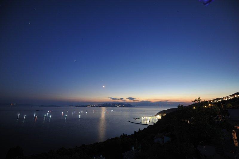 Villa CAMELIA. Panorama da varanda após escuro da lua à noite, com as luzes dos pescadores.