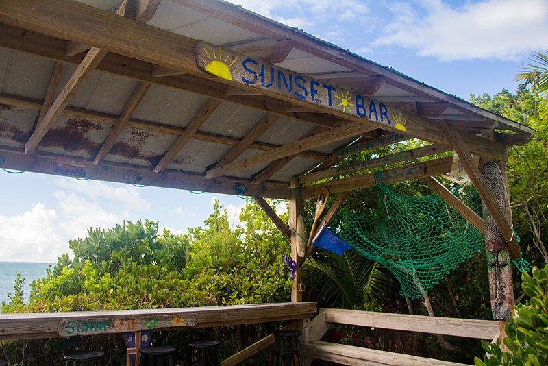 La puesta de sol de Tiki bar justo al lado de teh muelle en la línea de costa.