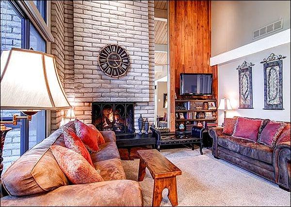 Grote gewelfde plafonds, open haard en flatscreen-tv in de woonkamer