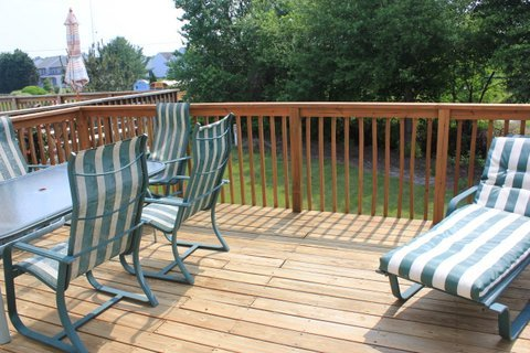Deck off kitchen with umbrella and dinner table for 6.