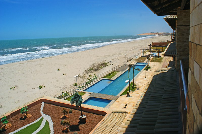 View from top floor terrace across the pool house, swimming pool, lake area and beach