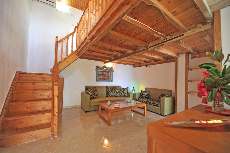 Villa CAMELIA. sala com dois sofás conversíveis cama de solteiro e de casal vivendo.