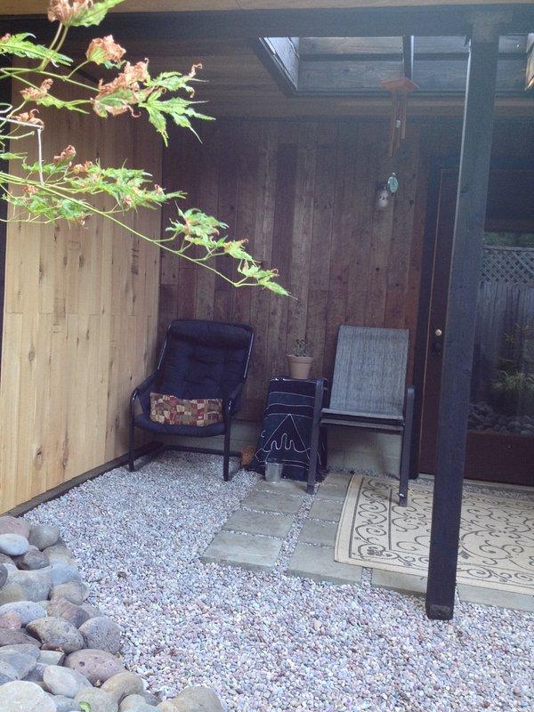 Il confortevole, coperto patio posteriore esterno si affaccia sul giardino Zen PNW