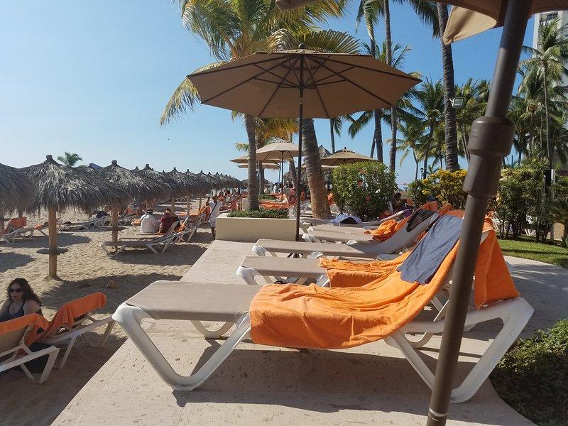 Des chaises longues sur le bord avec piscine derrière et plage en face.