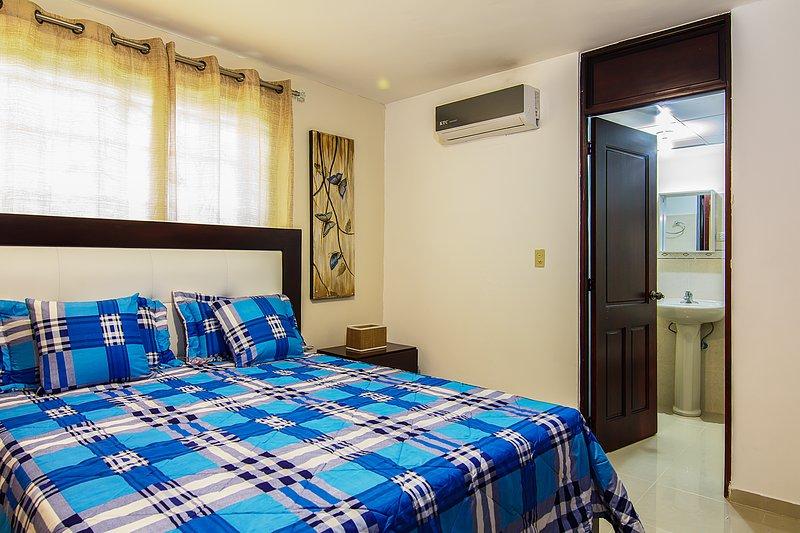 El dormitorio principal con TV, A / C y cuarto de baño