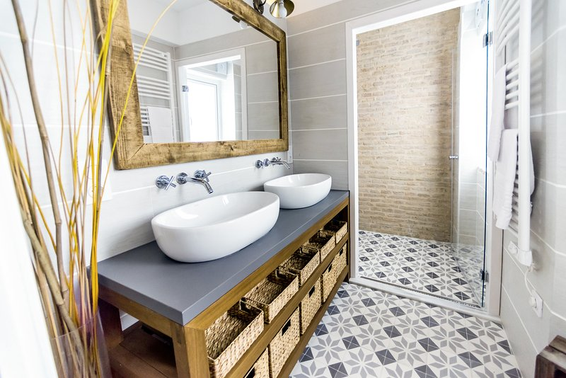 Salle de bains avec WC, douche de pluie, deux lavabos et chauffe-serviette