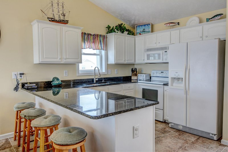 Granite countertops and a breakfast bar area, with a fully equipped kitchen