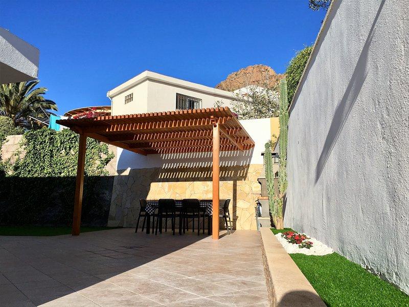 pergola en bois sur la terrasse arrière avec barbecue, table et chaises.