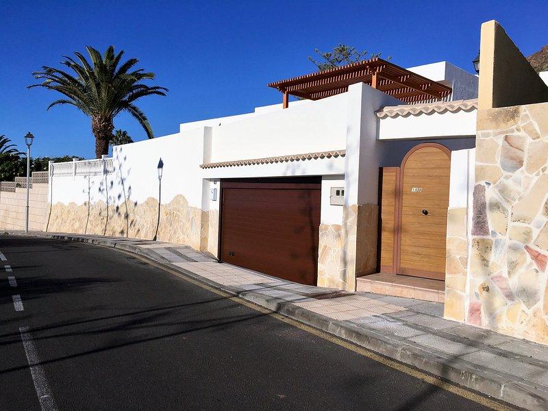 Façade de la villa. Double garage de taille avec porte automatique et l'entrée principale.