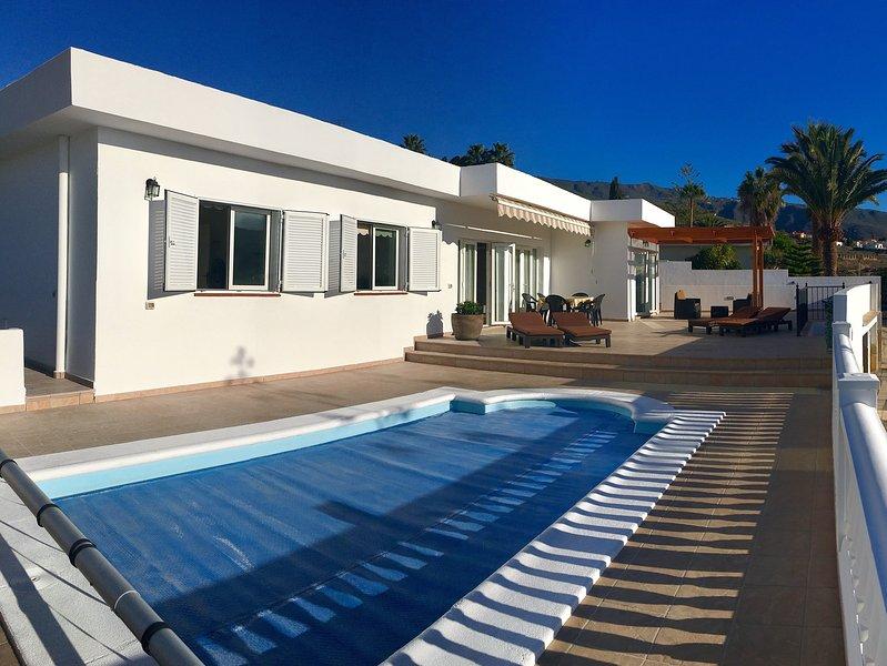 Frente w terraza. piscina climatizada, tumbonas, mesas y sillas, parasol y una pérgola de madera.