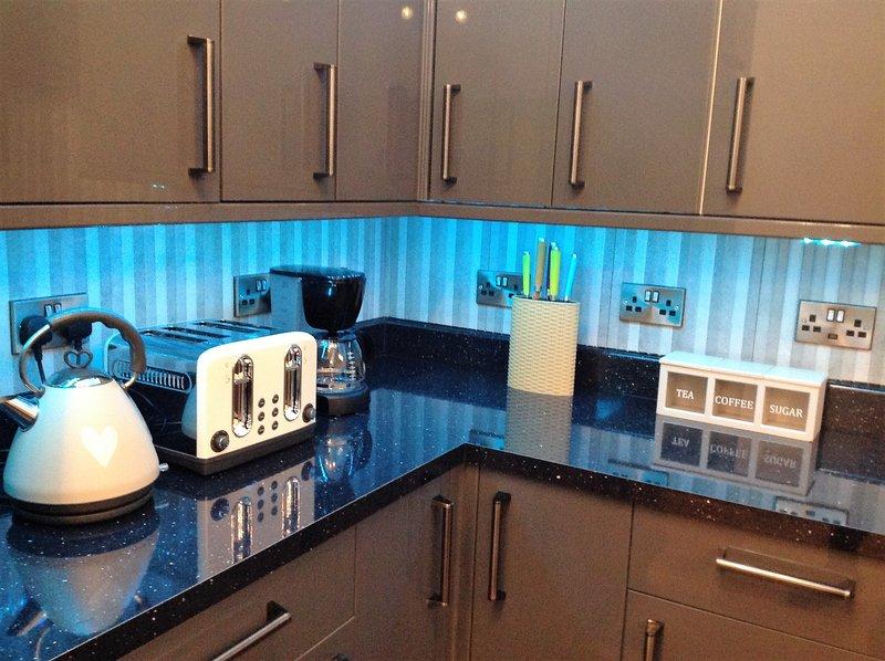 Uma visão mais próxima dos aparelhos de cozinha sob as luzes de néon azul.