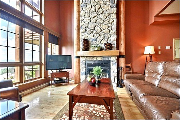 The Cozy Living Area with a Beautiful Stone Fireplace and Flat Screen TV