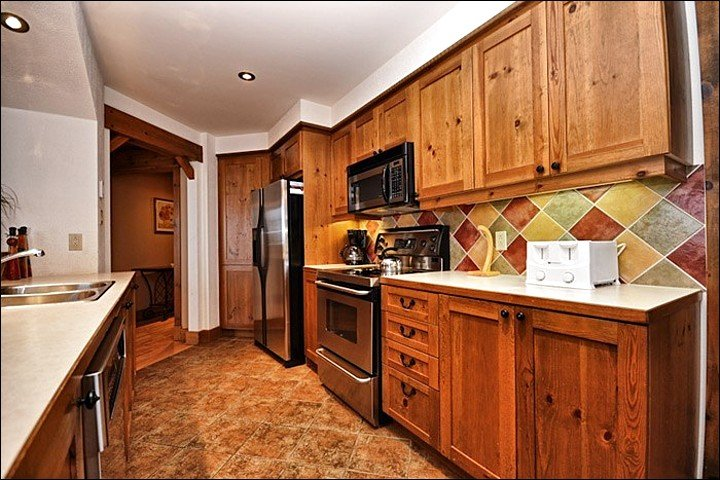 Fully Equipped Kitchen has Stainless Steel Appliances and Colorful Tile Accents