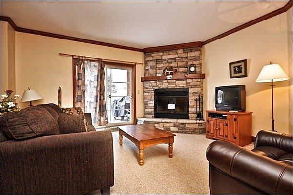 Sala de estar tem móveis confortáveis e uma lareira de pedra