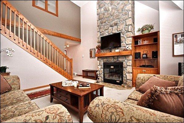 Le salon dispose de grandes fenêtres pittoresques et d'une cheminée en pierre confortable