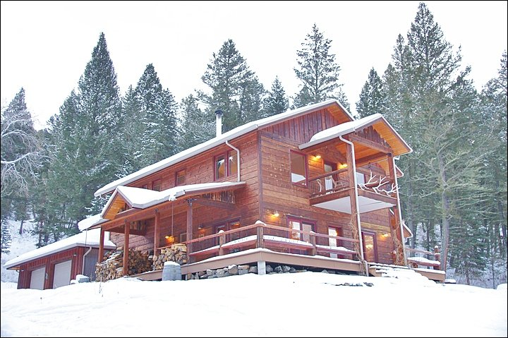A Covered Entrance, Wraparound Deck & Upper Balcony are Features of this Large Gallatin River home.