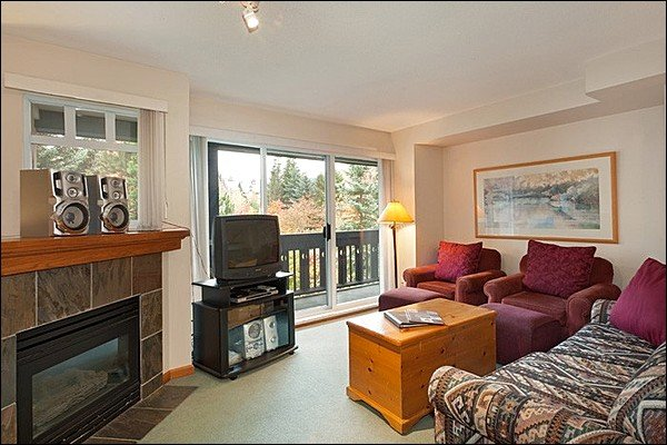 The Living Area Features a Gas Fireplace and a Private Balcony