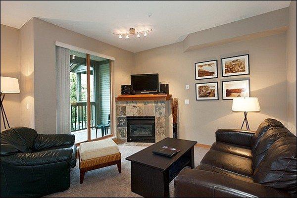 Espaçosa sala de estar com TV de tela plana e lareira a gás e acesso à varanda privativa