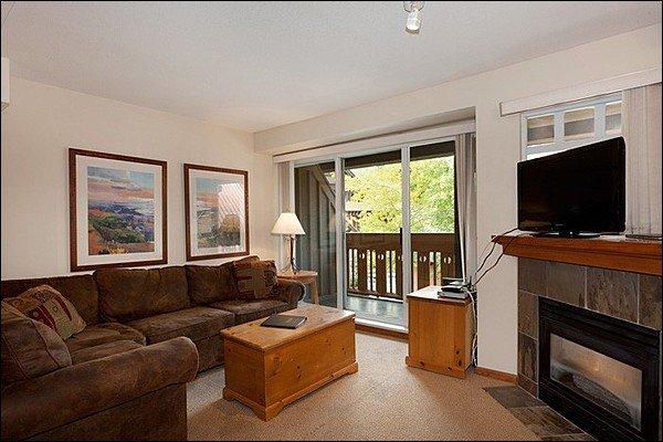Accogliente soggiorno con TV a schermo piatto, caminetto a gas e accesso privato al balcone