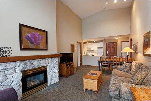 Área de estar com TV de tela plana e lareira a gás
