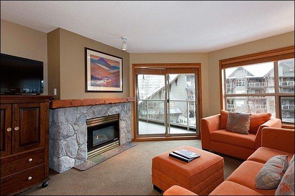 Área de estar moderna e atualizada com TV de tela plana, lareira a gás e acesso à varanda privativa
