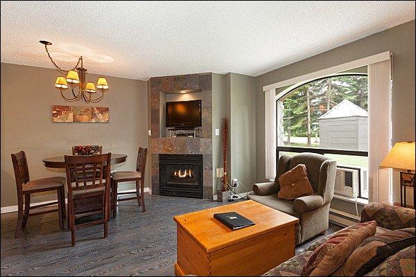 Vackert och modernt vardagsrum med plattskärms-TV, gas spis och trägolv