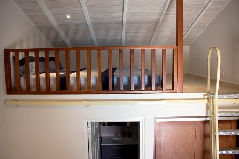 Escaliers à la galerie avec un lit