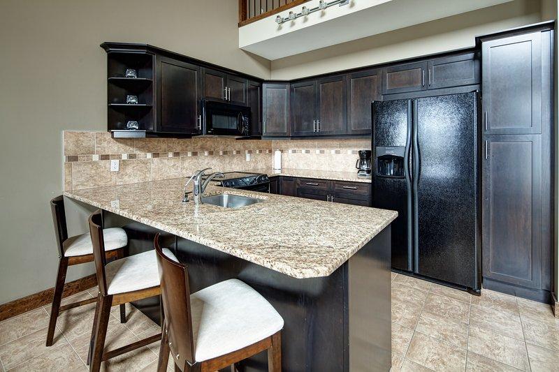 La cocina moderna y totalmente equipada cuenta con una encimera de granito.