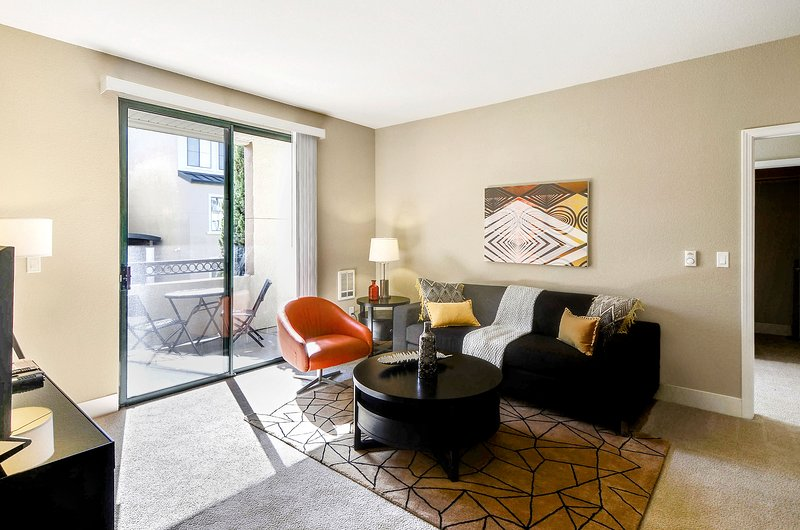 Living room with TV, private balcony access, and sleeper sofa