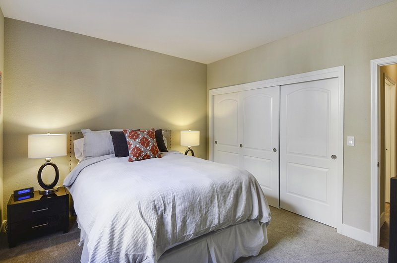 Bedroom with spacious closets, TV, and queen bed