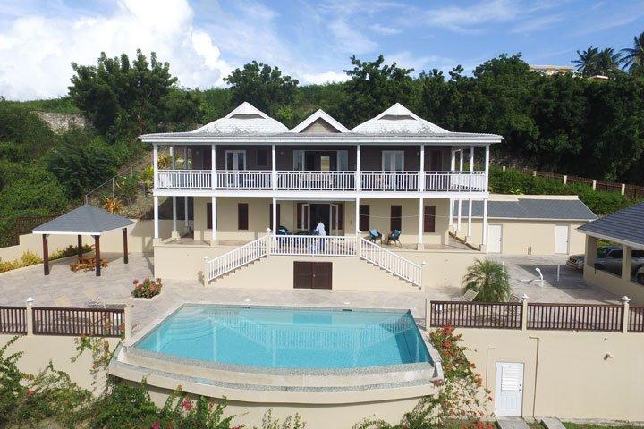 Infinity edge zwembad en een zonnedek in de voorkant van de villa.