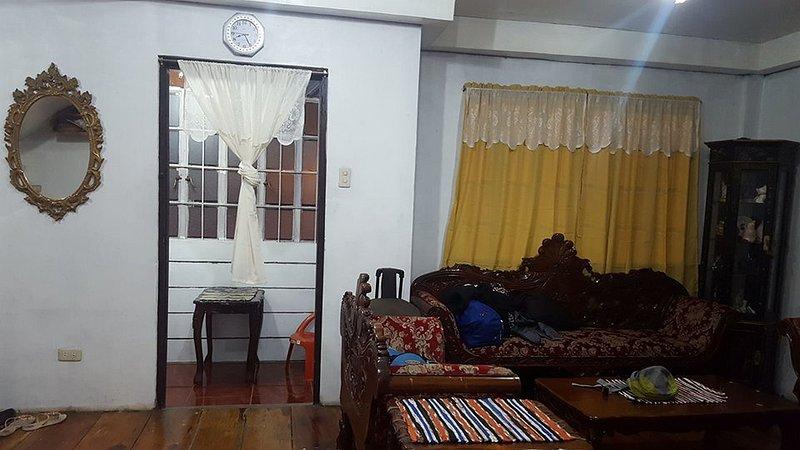 sala de estar con juego de sala de madera de narra, y balcón interior