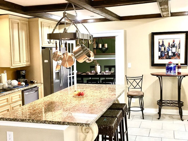 Large kitchen with granite counters, granite island and stainless steel cookware