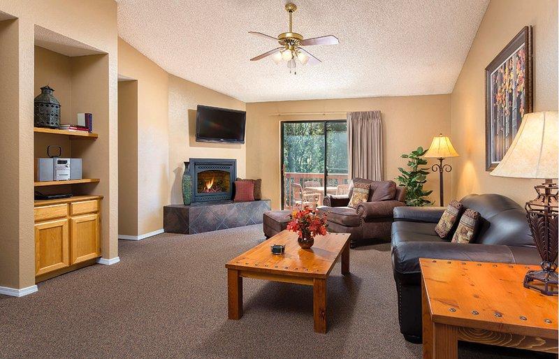 Relajarse en la sala de estar con cómodos sillones, una chimenea y un televisor de pantalla plana