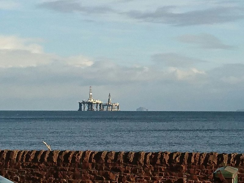 Roca baja en el fondo con protección de plataformas petrolíferas en el primer plano.