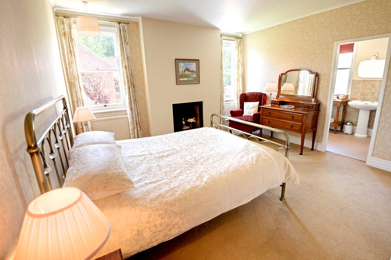 Spacious master bedroom with king size bed, fitted wardrobes & ensuite bathroom. Views of garden