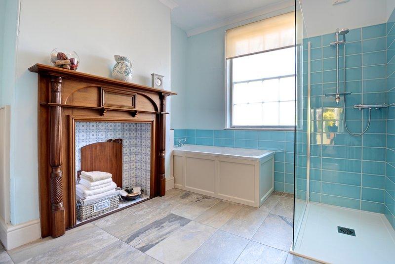 Large bathroom with low level, walk-in shower and underfloor heating. Next to ground floor bedroom