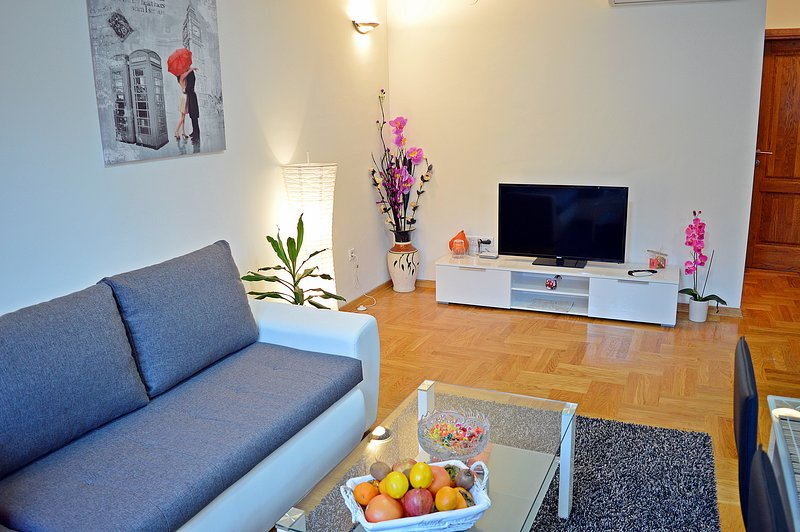 Living room with LCD TV, corner couch and coffee table.